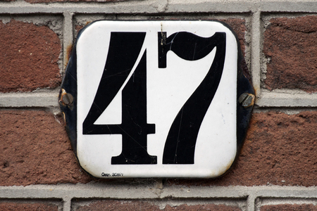 Enameled old house number 47 in black and wihte