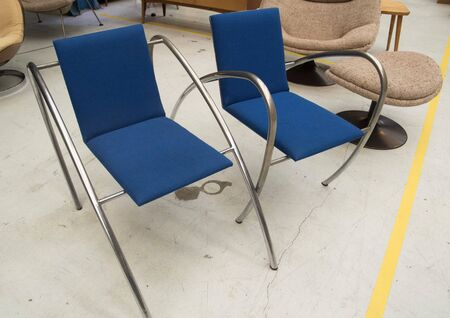 Fabric cobalt blue designer chairs with a stainless steel curved frame with round shapes.