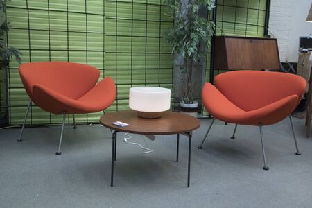 Two orange chairs with fabric covered with gray iron legs, with a table in front of them with a black iron frame with wooden tabletop. With a light green back wall and a gray concrete floor