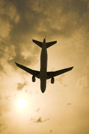 ジェット機が頭の上を飛んでいる太陽と、バック グラウンドで雲 写真素材