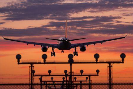 Airplane landing during sunset at Vancouver