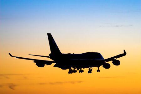 Large airplane landing during sunset