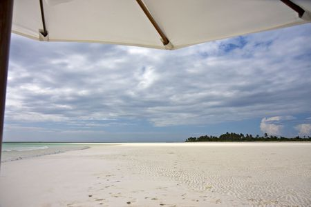 Relaxing under a beach umbrella on a white sanded beach