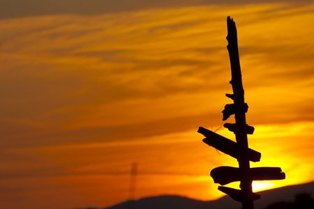 Old post silhouette with the sunset in the background Stock Photo