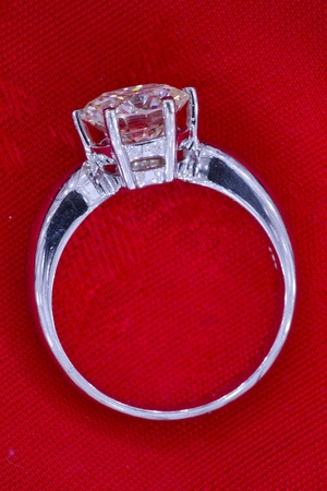 Two carat diamond ring with a red fabric background