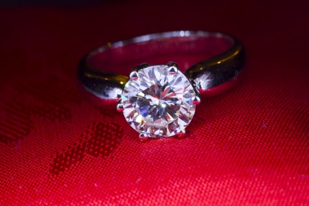 diamond ring: Two carat diamond ring with a red fabric background