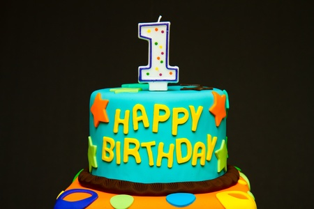 Happy first birthday fondant cake on a dark background Stock Photo