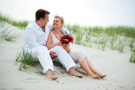 Just married couple sitting on a sand happily photo