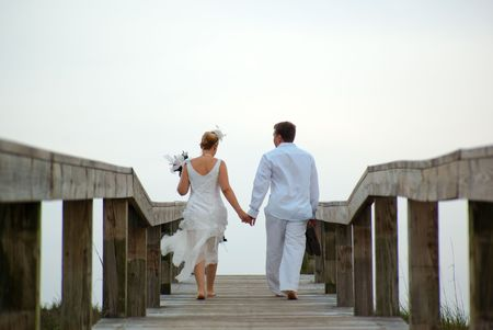 Bride and groom walking on a wooden bridge photo