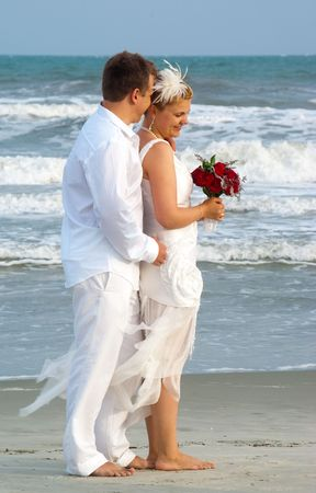 oceanfront: Embrace of bride and groom at the oceanfront Stock Photo