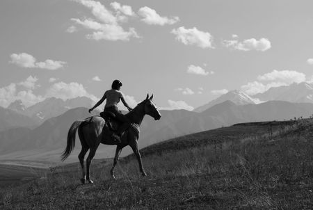 Girl riding a horse in the mountains photo