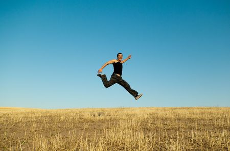 joyfully: Young handsome asian man jumping joyfully in the barley meadows