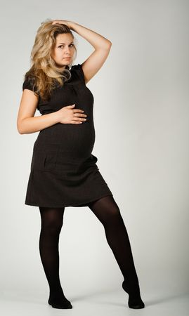 Beautiful young blond woman, seven months pregnant, in a black dress photo