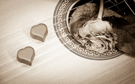 Red rose and two chocolate hearts on a guitar deck and strings, symbol of Valentines day and romance, sepia photo