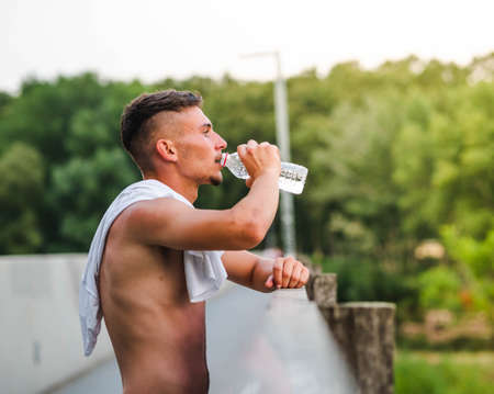 A young attractive sportsman drinking water after training - sport concept