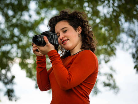 A curly Caucasian woman holding a camera during an outdoors shooting