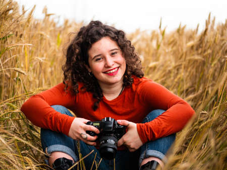A shallow focus shot of a beautiful young female with a professional photo camera Stock fotó