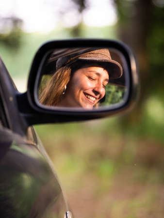 A picture of a brunette female in a black car with an amazing smile