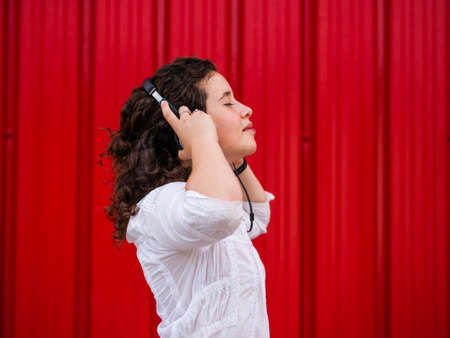 A young Caucasian woman happily listening to musing with headphones near a red wall