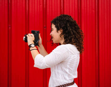 A young attractive female with an old professional photo camera against a red background