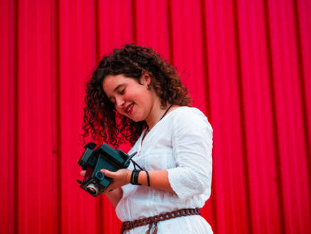 A young attractive female with an old professional photo camera against a red background 版權商用圖片
