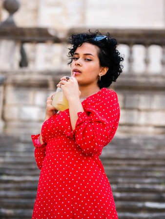 Brazilian female with a red dress. Young woman drinking juice