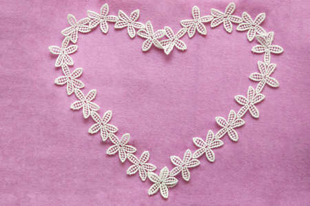 strapping: White romantic lacy heart on pink background on Valentines or Mothers day