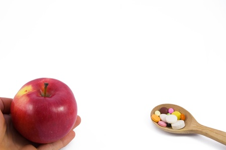 proposed: Proposed red apple on hand and spoon full of pills