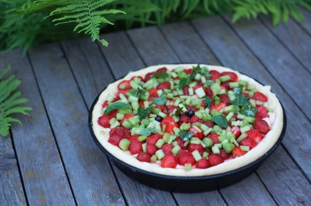 Half-finished tart with strawberry, rhubarb and peppermint photo