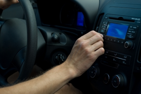 regulating: The driver is regulating some settings on car equipment Stock Photo