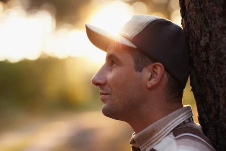 profil: Profil strzał młodego człowieka odwracając zamyśleniu w lesie wcześnie rano