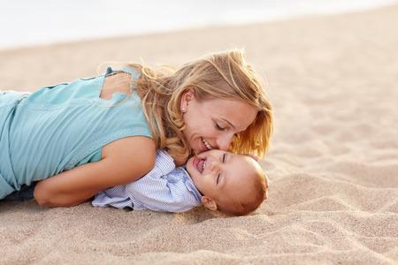 madre soltera: Joven madre hermosa que juega con su hijo bebé riendo en la playa