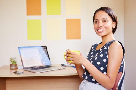 아름 다운 젊은 전문 여자의 초상화 그녀의 노트북 공개와 함께 그녀의 책상에 앉아