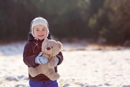 Portrait of a sweet little boy holding his teddy bear in a sunlit snowy field photo