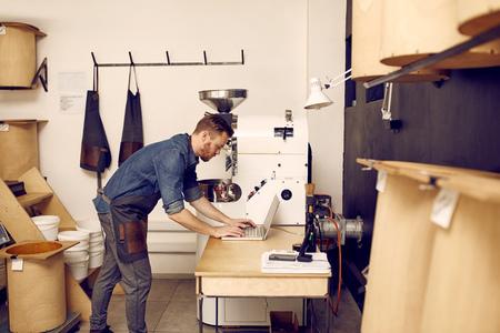 Jonge hipster man in een lichte en nette moderne werkruimte met behulp van zijn laptop met machines en eenvoudige opslagcontainers om hem heen Stockfoto