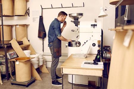 personas de pie: foto de cuerpo entero de un joven propietario de una moderna planta tostadora de café que huele una cucharada de granos de café recién tostados, que acaban de ser tostado por una máquina moderna