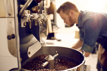Donkere en aromatische koffiebonen in een moderne roosteren machine met de wazig beeld van de professionele koffiebrander zichtbaar op de achtergrond Stockfoto