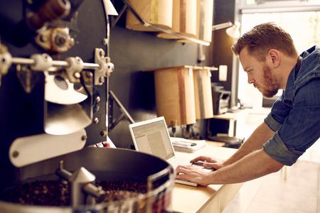 competencias laborales: Pequeño propietario de negocio de la tostadora que comprueba su ordenador portátil Foto de archivo