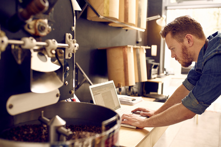 business: Proprietário empresarial pequeno de roastery verificar o seu laptop
