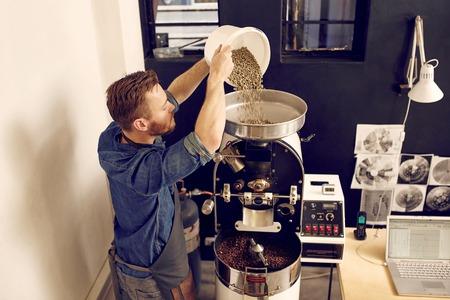 Hoge hoek shot van een man gieten van een partij van ruwe koffiebonen in de top van een moderne koffiebranderij machine, met vers gebrande bonen klaar aan de onderkant