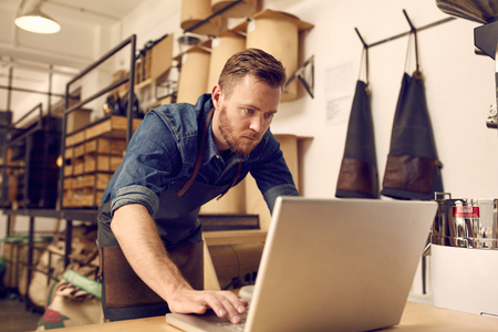 business owner: Handsome young male business owner looking serious while working on his laptop with a neat and tidy workshop behind him Stock Photo