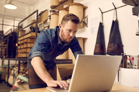 negócio: proprietário do negócio masculino novo considerável que olha sério enquanto trabalhava em seu laptop com uma oficina limpo e arrumado atrás dele