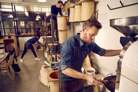 Mannen die in een moderne koffieboon Roastery met zakken van rauwe bonen en eenvoudige opslagcontainers georganiseerd voor de distributie Stockfoto