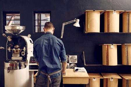 Rearview of a man in denim shirt working in a coffee roastery which has a modern roasting machine and simple, neat storage containers