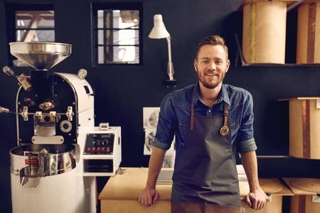 бизнес: Портрет улыбающегося человека глядя спокойно и уверенно в своем рабочем пространстве, где он жарится кофейные зерна и распределяет их