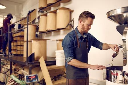 Man branden van koffie bonen met een moderne machine in een nette professionele werkruimte met opslag conatiners klaar voor distributie