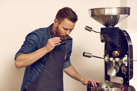 grano de cafe: Seria connoiseur grano de café junto a una moderna máquina de tostar, sosteniendo una cuchara con granos de café recién tostado con olor a ellos para comprobar si hay plenitud de aroma y sabor Foto de archivo