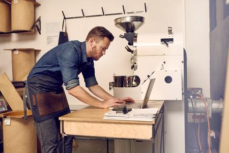 Professionele koffiebrander naast een modern koffieboon roosteren machine te typen op zijn laptop Stockfoto