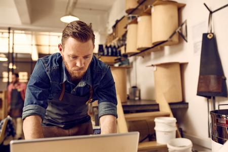 Knappe jonge ondernemer met een subtiele hipster stijl serieus werkt aan een lsptop met zijn lichte en nette moderne werkruimte achter hem