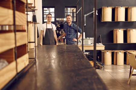 Portrait of two men in hipster style wear, smiling at the camera confidently in their modern workspace where they roast coffee beans with neat and simple storage containers